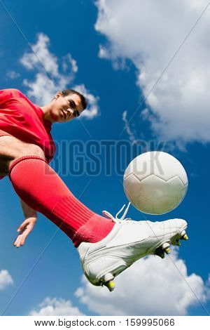 Soccer player controlling ball, toned image, sky in background