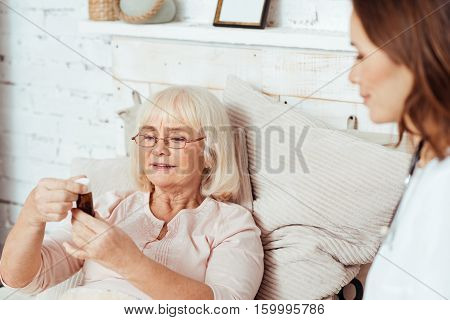 Examine it. Pleasant elderly woman holding bottle with pills and lying in bed while professioanl female dector visiting her at home