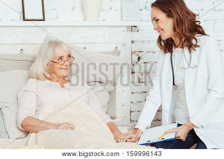 Cure with positivity. Pleasant professional doctor visiting elderly sick pleasant woman at home and holding her hand while giving a piece of advice.