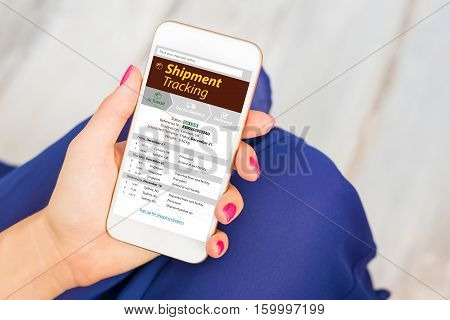 Shipment tracking on mobile phone in womans hand