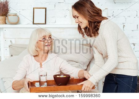 Caring granddaughter. Pleasant smiling young woman holdign tray and takign care of her sick grandmother who is lying in bed at home