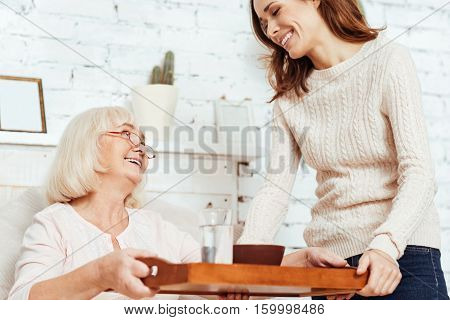 In elated mood. Low angle of pleasant joyful woman holding tray and takign care of her sick grandmother who is lying in bed at home