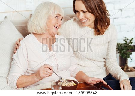 Thank you for support. Pleasant elderly delighted woman having breakfast and lying in bed while her beautiful caring granddaughter takign care of her
