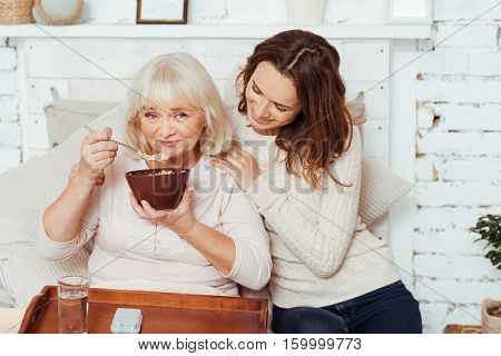 Family bounds.Pleasant delighted elderly woman sitting in bed and eating outmeal while her loving young granddaughter taking care of her