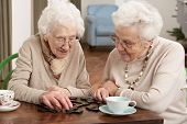 stock photo of day care center  - Two Senior Women Playing Dominoes At Day Care Centre - JPG