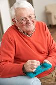 Senior Man Sorting Medication Using Organiser At Home