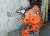 stock photo of countersink  - drilling holes in a brick house - JPG