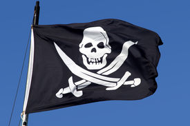 stock photo of pirate ship  - A pirate ship flag blowing in the breeze - JPG