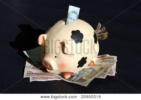 piggy bank with mexican money on black