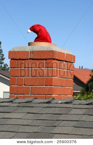 Santa Claus goes down a chimney with only his hat left showing