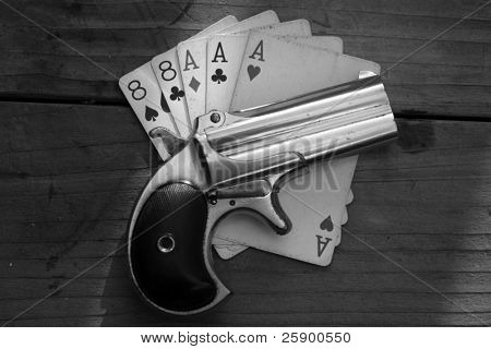 "Circa 1889, Model 95, Type II Model 3 Double Derringer, on antique wooden table aces and eights aka a ""dead mans hand"" in black and white for antique look"