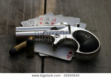 "Circa 1889, Model 95, Type II Model 3 Double Derringer, on an antique wooden table with aces and eights aka a ""dead mans hand"""