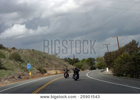 a couple of bikers ride their scooters down a two lane road with grey skys
