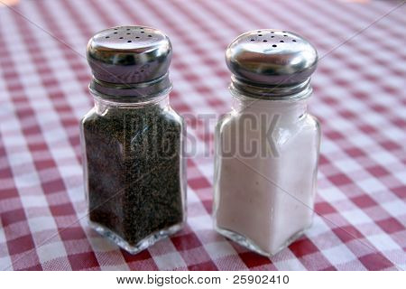 salt and pepper shakers on a red and white table cloth