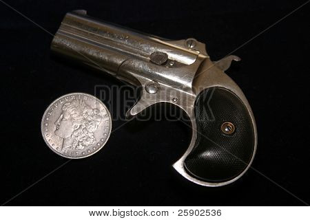 1889 darringer pistol with an 1887 Morgan silver dollar on blue velvet