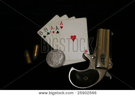 1889 darringer pistol with spare shells a  Morgan Silver Dollar, spare shells and aces and eights on blue velvet