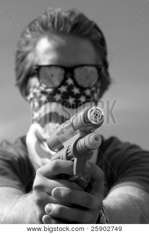 an insane young man wearing Hypnoitic Glasses and an American Flag bandanna holds a Squirt Gun in black and white
