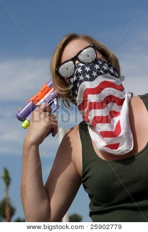 an insane young woman wearing a mask and hypnotic glasses woman points a squirt gun directly at her head