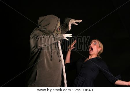 an innocent young woman shreaks in fear as she is about to be attacked by a gas mask wearing fiend in an apocylopic post nuclear future