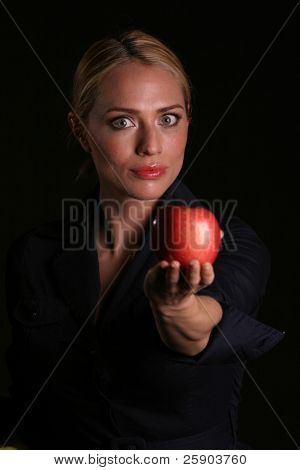 a healthy fit woman hands a fresh red apple to YOU the viewer healthy eating concepts eve passing adam an apple from the tree of knowledge concept
