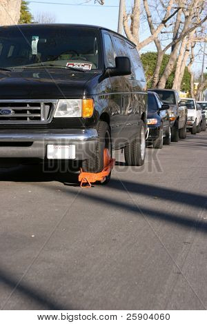 a boot clamp on a van parked where it is not supposed to be