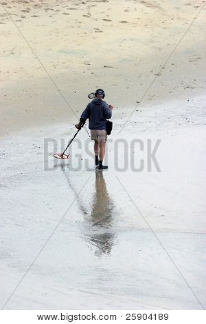 a unidentifiable person searches for burried Treasure with a metal detector in Huntington Beach California aka Surf City