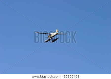a single engine floatplane flys above Seattle Washington and the pacific northwest.