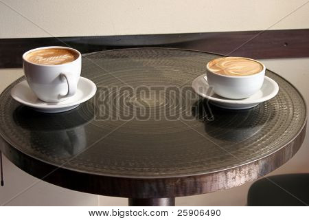"two latte's with ""Latte Art sit on a table in one of  Seattle Washingtons many coffee shops in Pike Place Market aka Farmers Market"