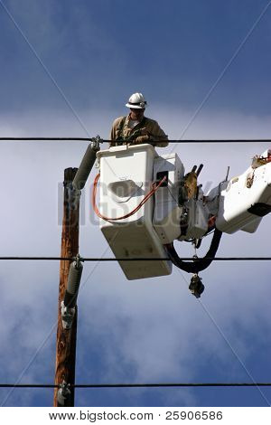 Workers in a man lift aka bucket lift prepare to remove and replace a 95 foot utility pole broken by a car accident