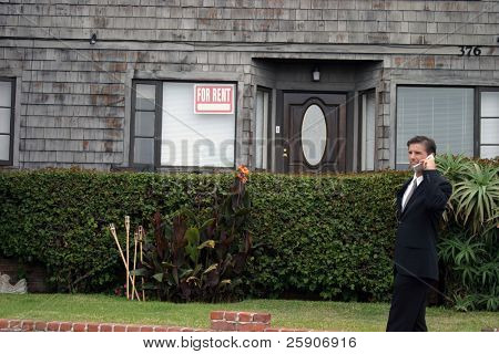 a realtor, or business man, or renter or building owner, talks on his cell phone while outside his home with a for rent sign in the window