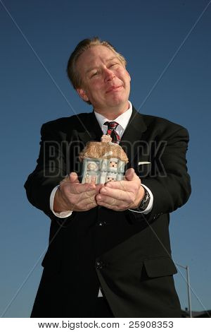 A Handsome and Friendly Realtor holds a house in his hands representing the concept of Home Ownereship, and securtiy