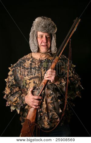 a man in camoflauge and a furry hat holds an antique
