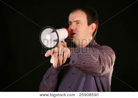 a man makes his demands known by speaking loudly through a megaphone and pointing his finger directly off camera with focus on his finger and hand
