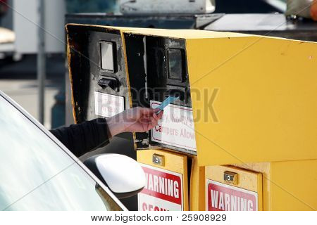 a human hand reaches for a parking ticket at a self service parking lot