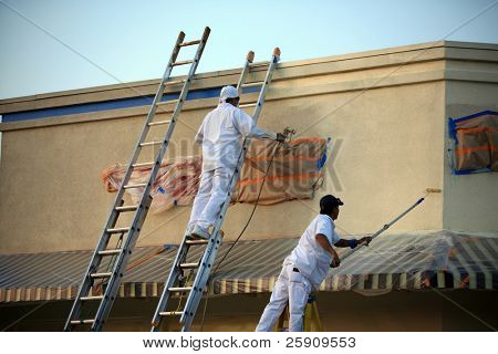 unidentifiable painters painting a building