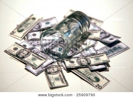 a shot glass lays upon a pile of miniature one hundred and twenty dollar bills, representing the high price of liquor and other economic slump concepts