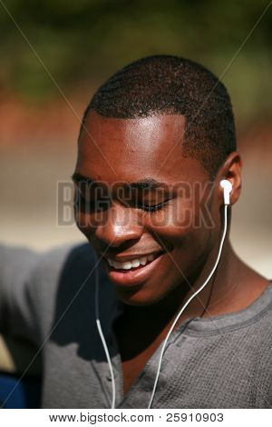 an african american male model listens to music on his personal mp3 music player