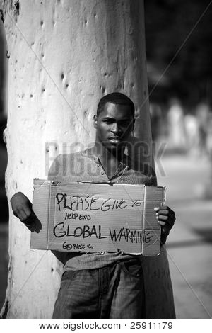 a man asks for donations to help stop Global Warming with his cardboard sign in black and white