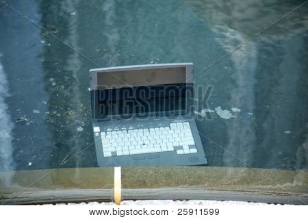 Computer damage concepts Laptop computer submerged in a pool of water