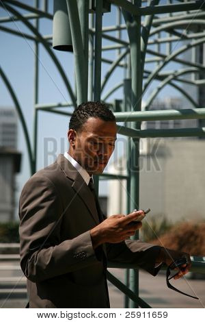 an african american business man text messages on his cell phone outside of his office building