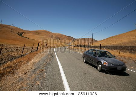 a car drives past on a Long and Winding Road
