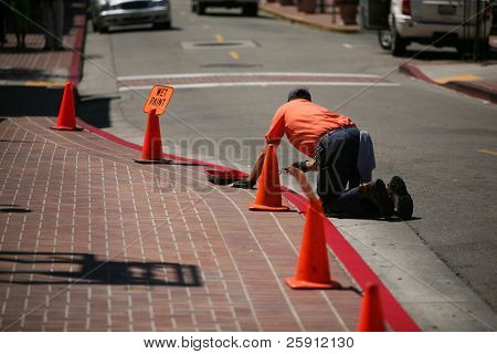 "an unidentifiable worker paints a red ""no parking"" stripe on a street curb"