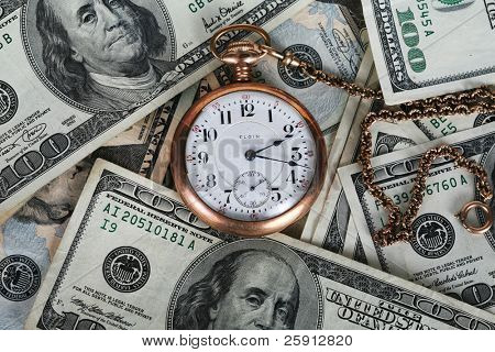antique pocket watch on a pile of money representing the saying