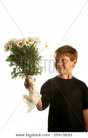 a young boy smiles as he holds a bunch of white daisies isolated on white