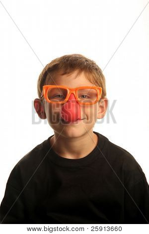 a young boy smiles while wearing funny clown nose glasses isolated on white
