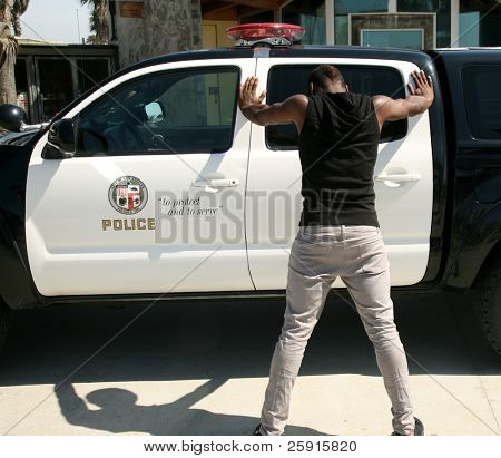 a young black man is up against a police car with his feet spread