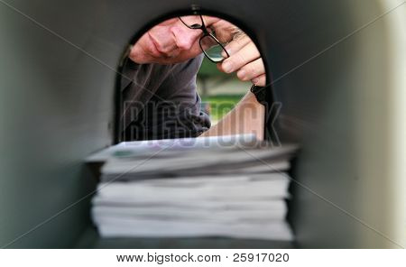 A man delivering or recieving mail in a mailbox