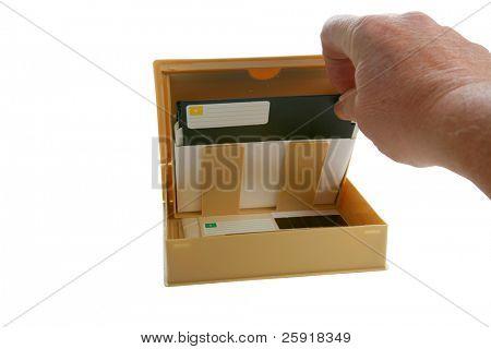 uma mão remove um disco de disquete de 5,25 polegadas de seu caso isolado no branco com espaço para seu texto ou im