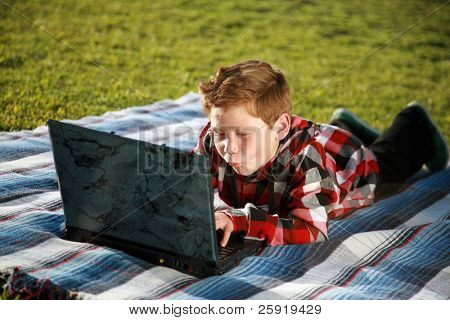 a young boy uses a laptop outside in the grass