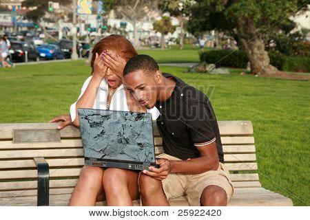 ein junges Paar Afroamerikaner sind schockiert zu was finden sie bei der Verwendung von eines Laptop-Computers außerhalb